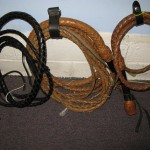 """Three of the Gery Deer's original cowhide, swivel-handled American bullwhips. (From Left) 10 foot, hand-dyed black with 1/2 inch flat latigo fall; 24-foot, brown with modified """"Australian styled"""" fall and popper; 6-foot, brown with modified fall and popper."""